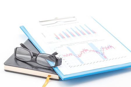 Concept of business graph, glasses on clipboard and notebook. photo