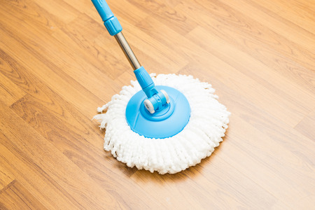 wood floor: Cleaning by use modern mop on laminated wood floor.