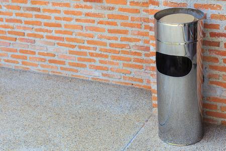 discard: Garbage bin of steel stainless wall brick background.