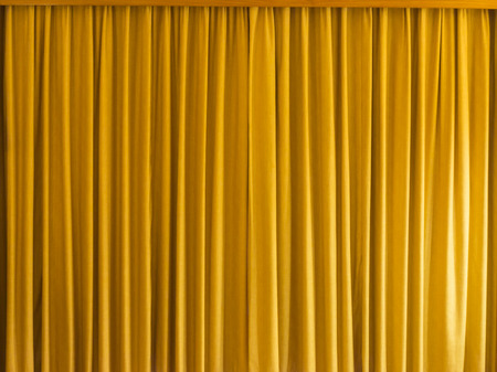 sipario chiuso: tenda gialla con telaio per sfondo e la trama.