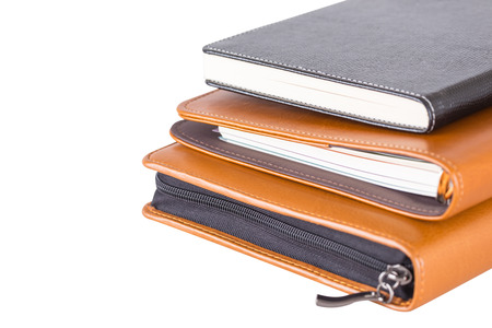Stack brown and black leather diary books  isolated on white background. Standard-Bild