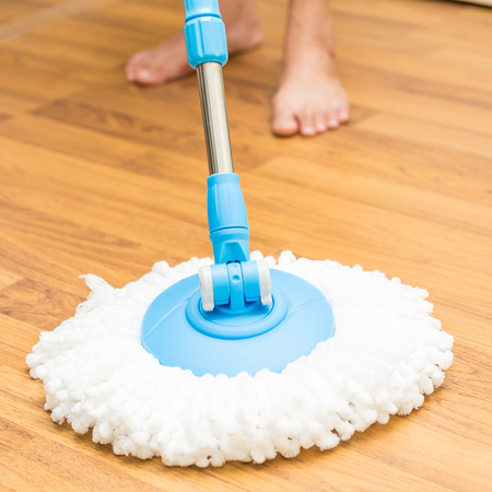Cleaning by use modern mop on laminated wood floor.