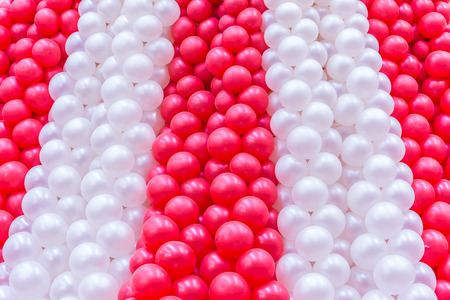 Red and white balloons many in row on background.