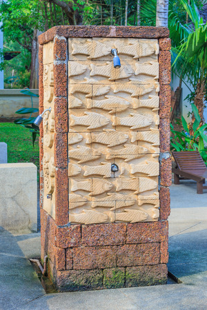 Outdoor shower head with brick wall fish statue.