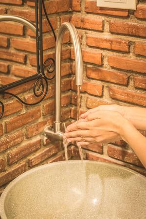 Hand washing at sink in bathroom, vintage filter.