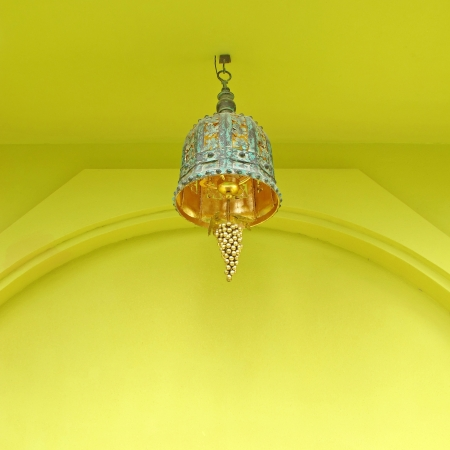 ornate lamp against yellow wall                photo