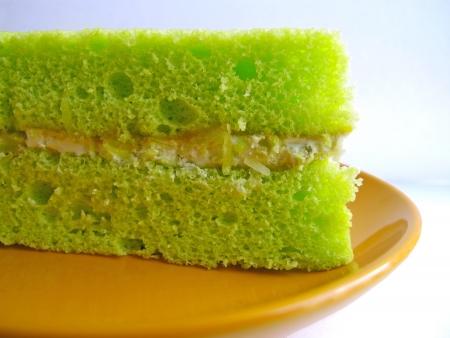 sponge cake stuff with cream and coconut on a orange plate Imagens