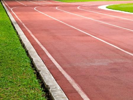 running vermelha faixas com grama verde