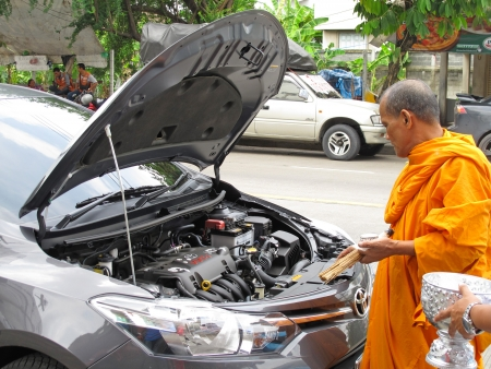 anoint: BANGKOK - JUNE 13: Monk sprinkle holy water and make auspicious marking on a new car for the owners lucky and safety on June 13, 2013 in Bangkok, Thailand. Editorial