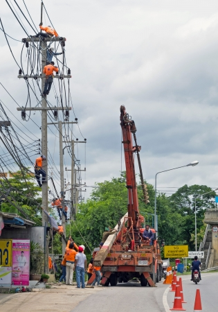 RATCHABURI, THAILAND - AUGUST 24: Electricians are installing electric post and wiring connections on August 24, 2013 in Ratchaburi, Thailand.