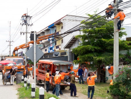 RATCHABURI, THAILAND - AUGUST 24: Electricians are connecting wires between two electric post on August 24, 2013 in Ratchaburi, Thailand.