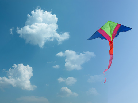 Colorful kite flying amidst fluffy clouds  Stock Photo