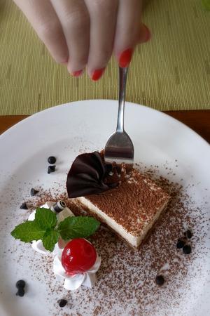 A fork in woman hand cutting off Tiramisu cake.