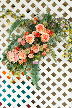 grate: A bouquet of artificial flower on white wooden grate.
