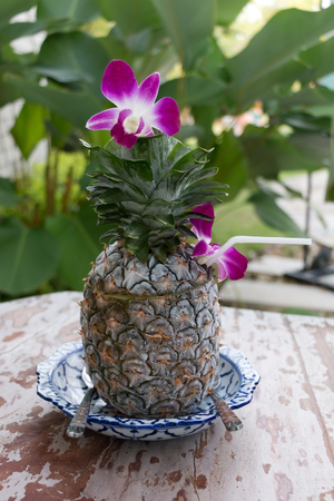 Freezing pineapple decorated with orchid on wooden table in green garden.