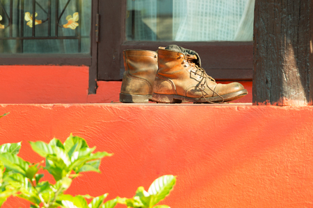 army boots: A pair of leather boots with dirt from grass lay in front of the garden resort door in sunshine morning. Stock Photo