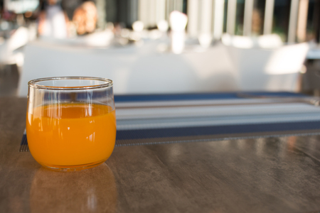 A glass of orange juice for breakfast on wooden table with napery in restaurant.