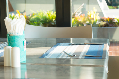 Simple table setting in restaurant with light and shadow of morning sunshine, soft focused.