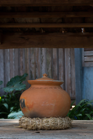 Old pottery pot in front of Thai home contain rainwater to serve neighbour; display ancient Thai culture in tourist attraction. Stock Photo