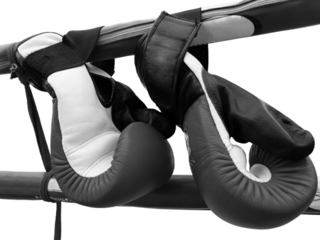 A pair of Thai boxing gloves hangs on the cord of boxing ring in black and white. Stock Photo