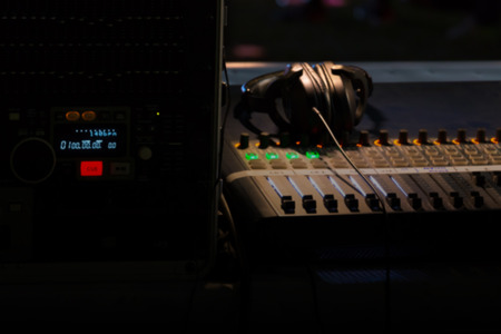 Blurry background of digital mixer and fader for music recording, radio or tv broadcasting in dark light. Stock Photo