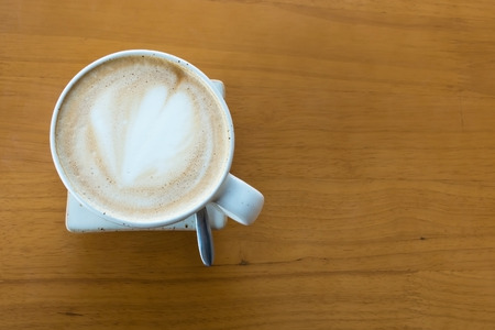 A cup of hot coffee with heart shape of latte art on wooden table. Stock Photo