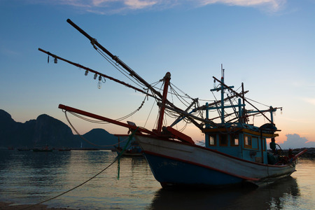 Old wooden fishing boat anchored at the beach in sunrise scene at Pranburi, Thailand.