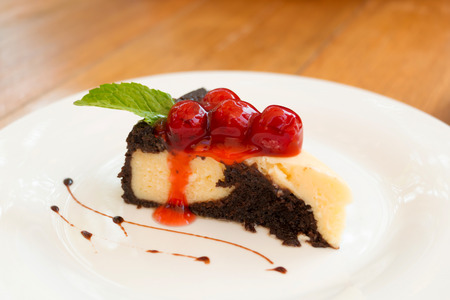 Brownies cheesecake topping with cherry in close-up.