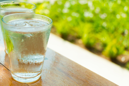 Blurry image of glasses of cool water on wooden table in green garden.