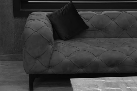 Black and white image of vintage sofa with backrest pillow in room.