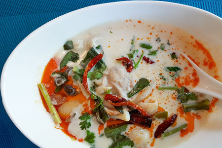 Thai Chicken Soup in Coconut Milk or Tom Kha Gai in Thai language served on white bowl (shoot by mobile camera). Stock Photo