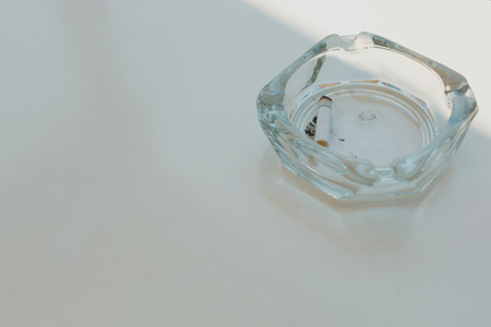 Glass ashtray with one cigarette in it on white table in different light and shade.