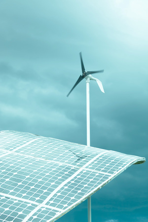 Solar cell panels and wind turbine that spinning in dam weather day. Stock Photo