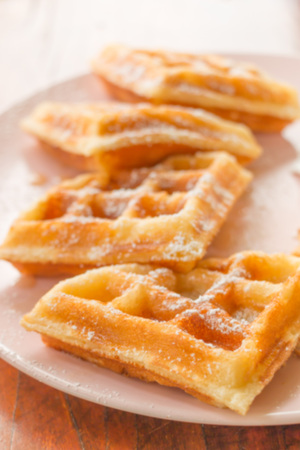 Blurry stack of waffle with icing sugar on pink plate on wooden table.
