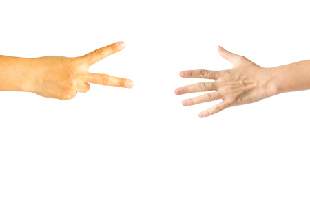 Two hand playing rock paper scissors; one hand showing scissors sign and another hand showing paper sign. Stock fotó