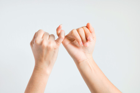 Dwie ręce chwytają mały palec razem, obiecując i / lub prosząc o wspólne pogodzenie.