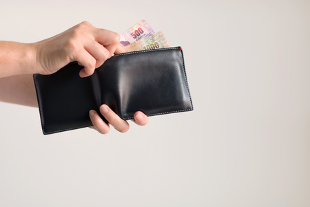 Hands holding a wallet and bring many Thai banknotes out from it for paying.
