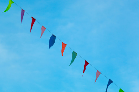 Colorful triangle flags diagonal with the blue sky. Stock Photo