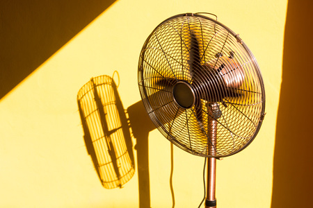 Vintage fan and its shadow from sunlight through the window. Imagens