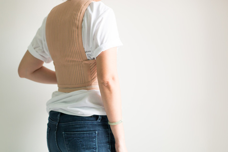 A woman wearing back support corsets for protect her back and reduce back pain.