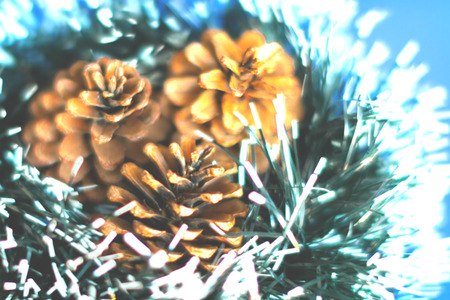 Blurry background of decorative pine cones for Christmas lay on green tassel in vintage effect image style.