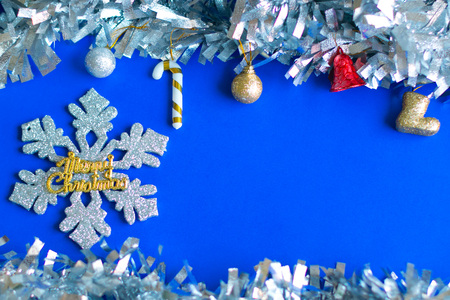 Christmas ball and decorative stuffs on blue background with silver snowflake and gold Merry Christmas text to be greeting card.