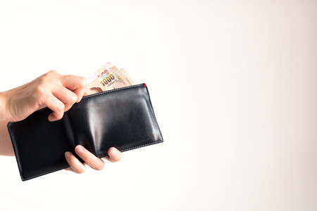 Hands holding a wallet and bring Thai banknotes value 1000 and 500 Baht out from it for paying on white background. 写真素材
