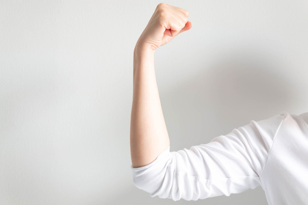 Close-up of woman hand showing fist and raising up showing muscle on white background; concept of strong and confident woman.