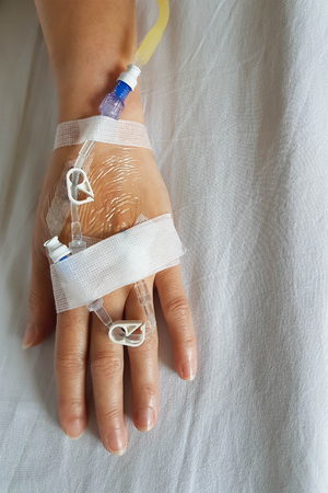 Close-up of hand that have infusion needle and IV tube for intravenous infusion on background of white bed sheet of patient bed; shoot by mobile camera.