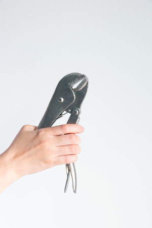 Vertical image of a hand is holding pincers pliers on white background with copy space.