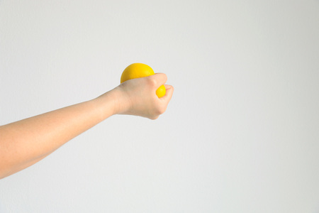 A hand hold and pressing yellow squishy ball (squeezing ball toy) for exercise muscle and relieve strain from work on white background; concept of health care and medical.