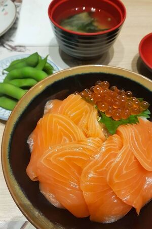 Salmon donburi (japanese rice with raw salmon and salmon roe) served with miso wakame soup and edaemame on table at restaurant; shoot by mobile camera. 写真素材
