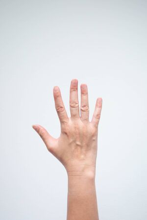 Vertical image of caucasian raise hand on white background (shoot close-up and focus only the right hand; shoot at back side).