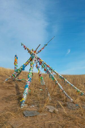 Shaman wood with many of colorful ribbons tied on them; on the way to the stupa at top of Ogoi island at Baikal lake; Siberia in Russia. concept of religion belief.